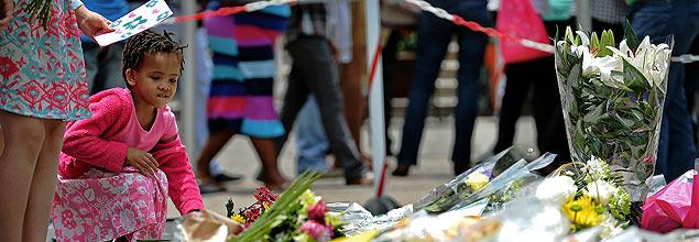 Una niña deposita flores en honor a Nelson Mandela, en un barrio de Johannesburgo. Fotografía: Carl de Souza-AFP