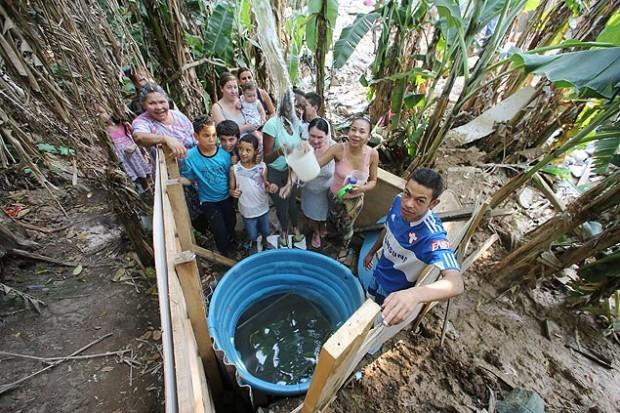 Habitantes de un barrio de la zona sur de São Paulo hicieron un pozo en un terreno  baldío para sacar agua del subsuelo, después de pasar cuatro días sin suministro. Fotografía: Rivaldo Gomes/Folhapress.