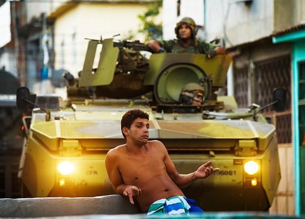 Un hombre posa frente a un vehículo blindado de las Fuerzas  Armadas, durante la ocupación del Complexo da Maré, en abril de 2013. Fotografía: Daniel Marenco/Folhapress.