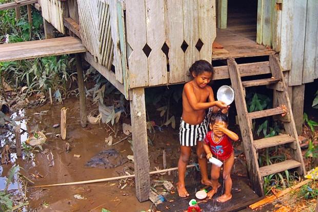 Niños duchándose con agua del río junto a la puerta de su casa. Fotografía: Luna Gámez.